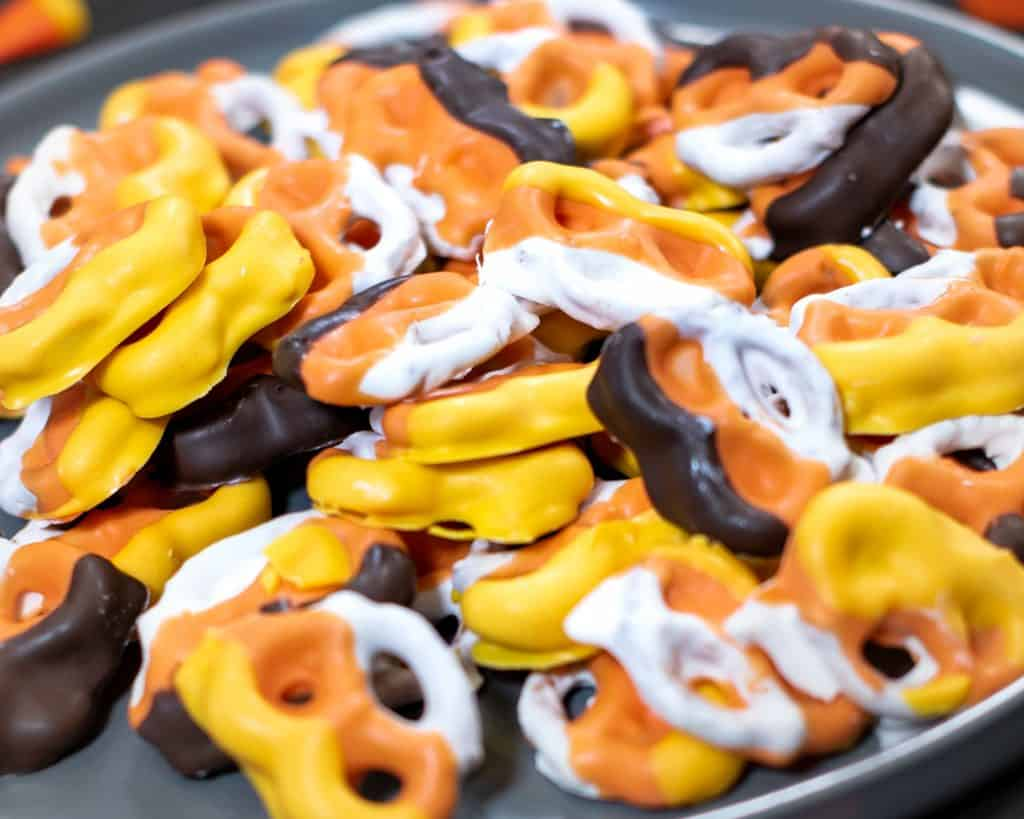 small pretzels covered with orange, yellow, and white chocolate