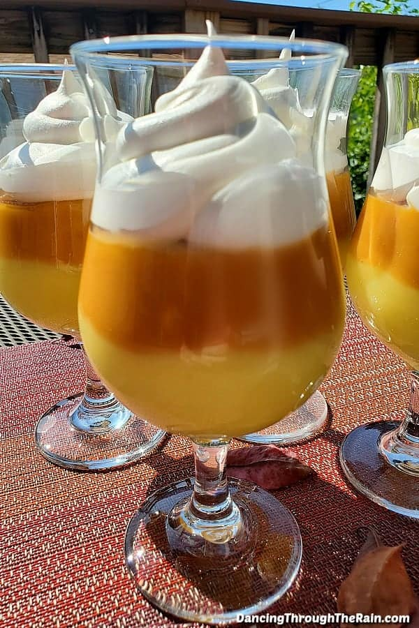yellow, orange, and white topping pudding desserts in glass cup