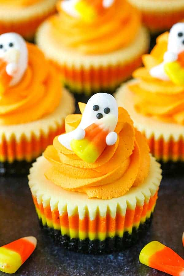 Layered cupcake with yellow, orange, and white sections. topped with orange icing and edible ghost candy