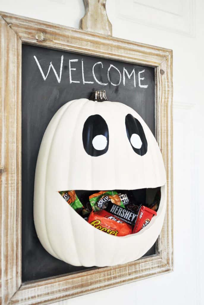 white pumpkin with mouth to hold candy, mounted on flat board